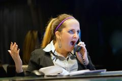 Kvinnasammanträde på hennes skrivbord som arbetar och svarar en påringning arkivfoton