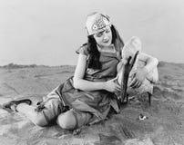 Kvinnasammanträde på jordinnehavet en pelikan i hennes arm (alla visade personer inte är längre uppehälle, och inget gods finns S arkivbild