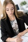 Kvinnasammanträde på kontoret och underteckning av några dokument Royaltyfri Foto