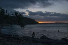 Kvinnasammanträde på kusten i molnig afton arkivbild