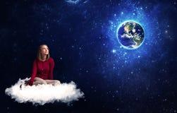 Kvinnasammanträde på molnet som ser planetjord Arkivfoto