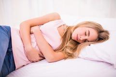 Kvinnasammanträde på säng och lidande från buk- smärtar Arkivbilder