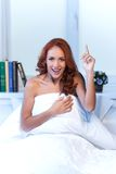 Kvinnasammanträde på säng under täcket och le Fotografering för Bildbyråer