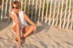 Kvinnasammanträde på sand på stranden som ser solnedgången arkivbilder