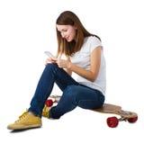 Kvinnasammanträde på skateboarden och använda den smarta telefonen Arkivbilder