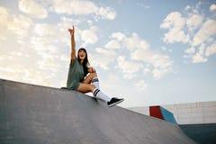 Kvinnasammanträde på skateboardramp på skridskon parkerar arkivbilder