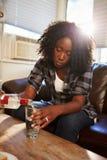 Kvinnasammanträde på Sofa With Bottle Of Vodka royaltyfri bild