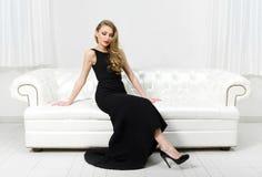 Kvinnasammanträde på soffan för vitt läder Royaltyfri Bild