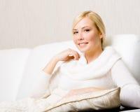 Kvinnasammanträde på soffan för vitt läder arkivfoto