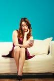 Kvinnasammanträde på soffan genom att använda mobiltelefonen Royaltyfri Bild