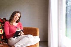 Kvinnasammanträde på soffan hemma och handstil i bok Royaltyfri Bild