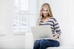 Kvinnasammanträde på soffan med bärbara datorn Arkivbilder