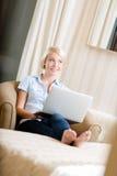 Kvinnasammanträde på soffan med bärbara datorn Arkivfoto