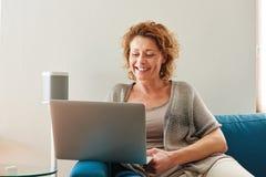 Kvinnasammanträde på soffan med den hemmastadda bärbara datorn arkivfoton