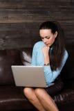 Kvinnasammanträde på soffan och användabärbara datorn Arkivbild