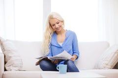 Kvinnasammanträde på soffan och den läs- tidskriften Arkivfoto