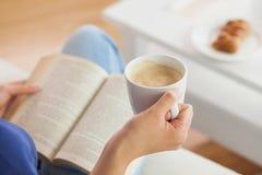 Kvinnasammanträde på soffan som läser en bok som rymmer hennes kaffe, rånar Royaltyfri Foto