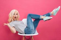 Kvinnasammanträde på stolen med lyftta ben fotografering för bildbyråer