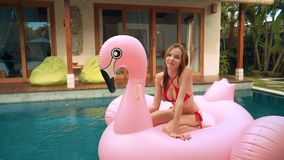 Kvinnasammanträde på stor uppblåsbar flamingo i pöl stock video