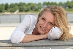 Kvinnasammanträde på stranden arkivfoto