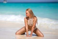 Kvinnasammanträde på stranden för sand för Zanzibar ` s den vita Royaltyfria Bilder