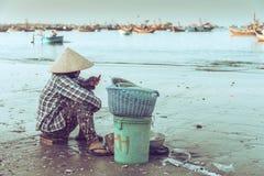 Kvinnasammanträde på stranden i Mui Ne, Vietnam arkivbild