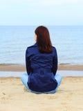 Kvinnasammanträde på stranden och blickar på havet arkivfoto