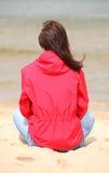 Kvinnasammanträde på stranden och blickarna på havet, sommartid royaltyfri bild