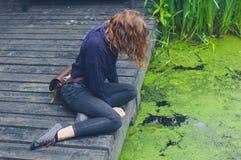 Kvinnasammanträde på trädäck vid dammet arkivbilder
