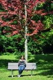 Kvinnasammanträde parkerar på bänken som läser en bok royaltyfri bild