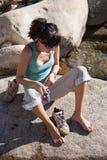 Kvinnasammanträde vaggar på att sätta på sockor royaltyfri foto