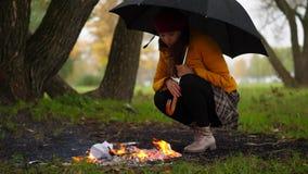 Kvinnasammanträde vid brand utanför med det stora paraplyet under regn stock video