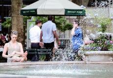 Kvinnasammanträde vid springbrunnen i Bryant Park Royaltyfria Bilder