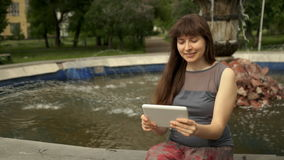 Kvinnasammanträde vid springbrunnen med minnestavlan stock video