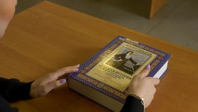 Kvinnasammanträdeläsning på tabellen Kvinnan öppnar boken, innan han läser lager videofilmer
