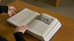 Kvinnasammanträdeläsning på tabellen Kvinnan stänger boken, når han har läst arkivfilmer