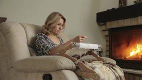 Kvinnasammanträdet vid spisen broderar modellen på tyget i en stol stock video