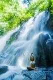 Kvinnasammanträdeyoga poserar i andlig avkopplingserenitet och meditation på att bedöva den härliga vattenfallet och regnskogen i arkivfoto