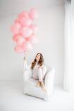 Kvinnasammanträde i en fåtölj och ett innehav per gruppen av rosa ballonger Arkivfoto