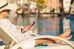 Kvinnasammanträde i stol vid simbassängen och användasmartphonen Arkivbild