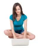 Kvinnasammanträde på golv med bärbara datorn Arkivbild
