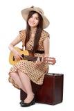 Kvinnasammanträde på hennes resväska, medan spela gitarren Arkivfoton