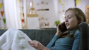 Kvinnasamtal på smartphonen på en soffa stock video