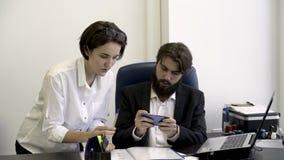 Kvinnasekreteraren visar viktiga dokument till hennes skäggiga framstickande som är upptaget med att spela smarta telefonlekar i  stock video