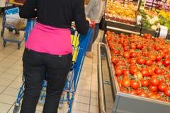 Kvinnashopping för livsmedel i supermarketanseende med henne tillbaka Arkivfoton