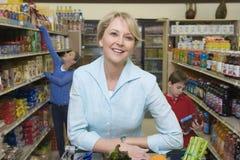 Kvinnashopping med ungar i supermarket Arkivbild