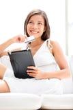 Kvinnashopping på minnestavladatoren med kreditkorten Fotografering för Bildbyråer