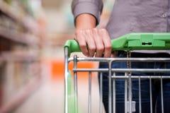 Kvinnashopping på supermarketen med trolleyen Royaltyfri Foto