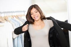 Kvinnashoppingaffären passar kläder Fotografering för Bildbyråer