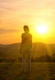Kvinnasilhouette på solnedgången Royaltyfria Bilder